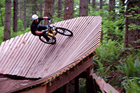 Person Riding Bike Around a Wooden Ramp