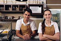 Young Man and Young Woman Wearing Aprons Standing Behind Counter