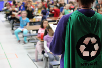 Person Wearing Cape with Recycle Symbol Facing Crowd of Students